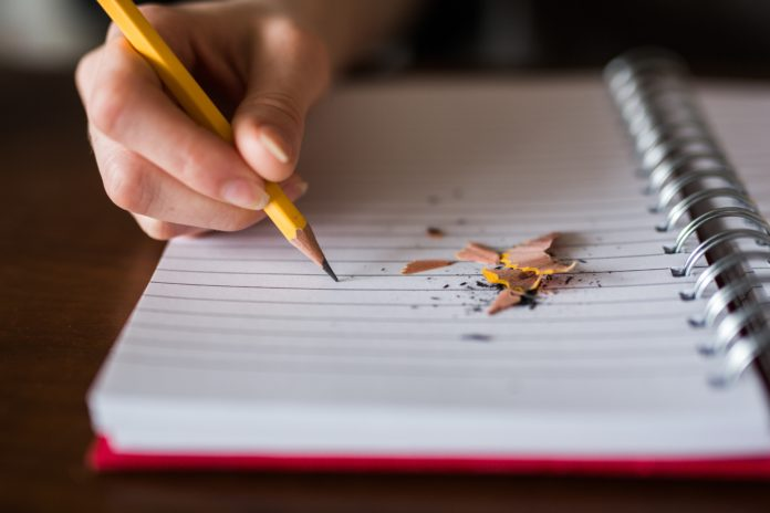 Picture of a hand holding a pencil, writing on a diary. Next to the pencil are pencil shavings strewn on the paper